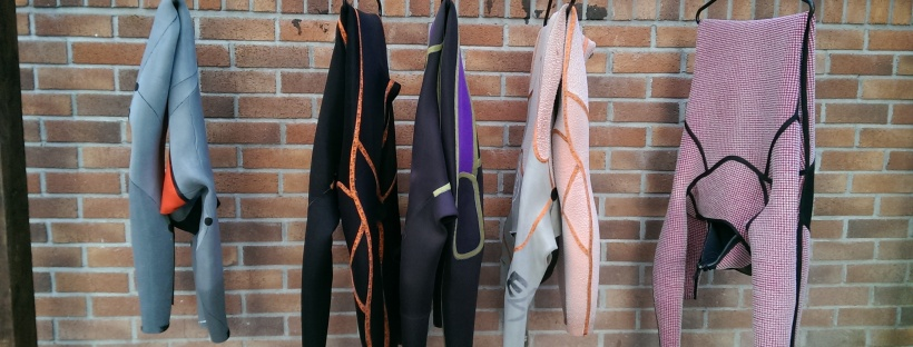 Wetsuits hanging up in St Ives Hostel, poem about wetsuits and watersports on Sea, Earth, Sky